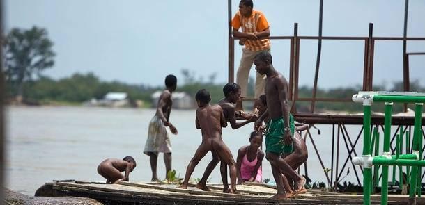 Internt fordrevne børn leger ved floden i byen Rio Sucio