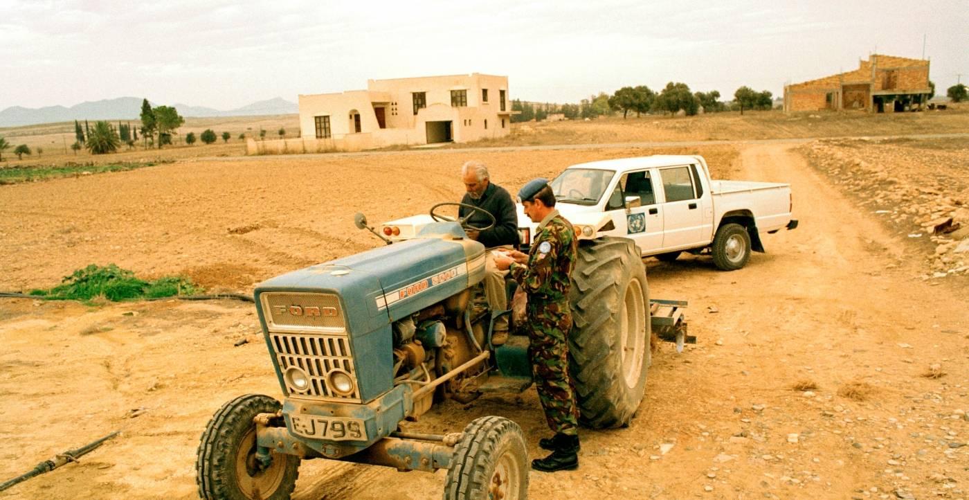 En britisk soldat fra FN's fredsbevarende styrke på Cypern, tjekker identitetspapirene til en cypriotisk bonde på en gammel traktor (Foto: UN Photo / John Isaac).