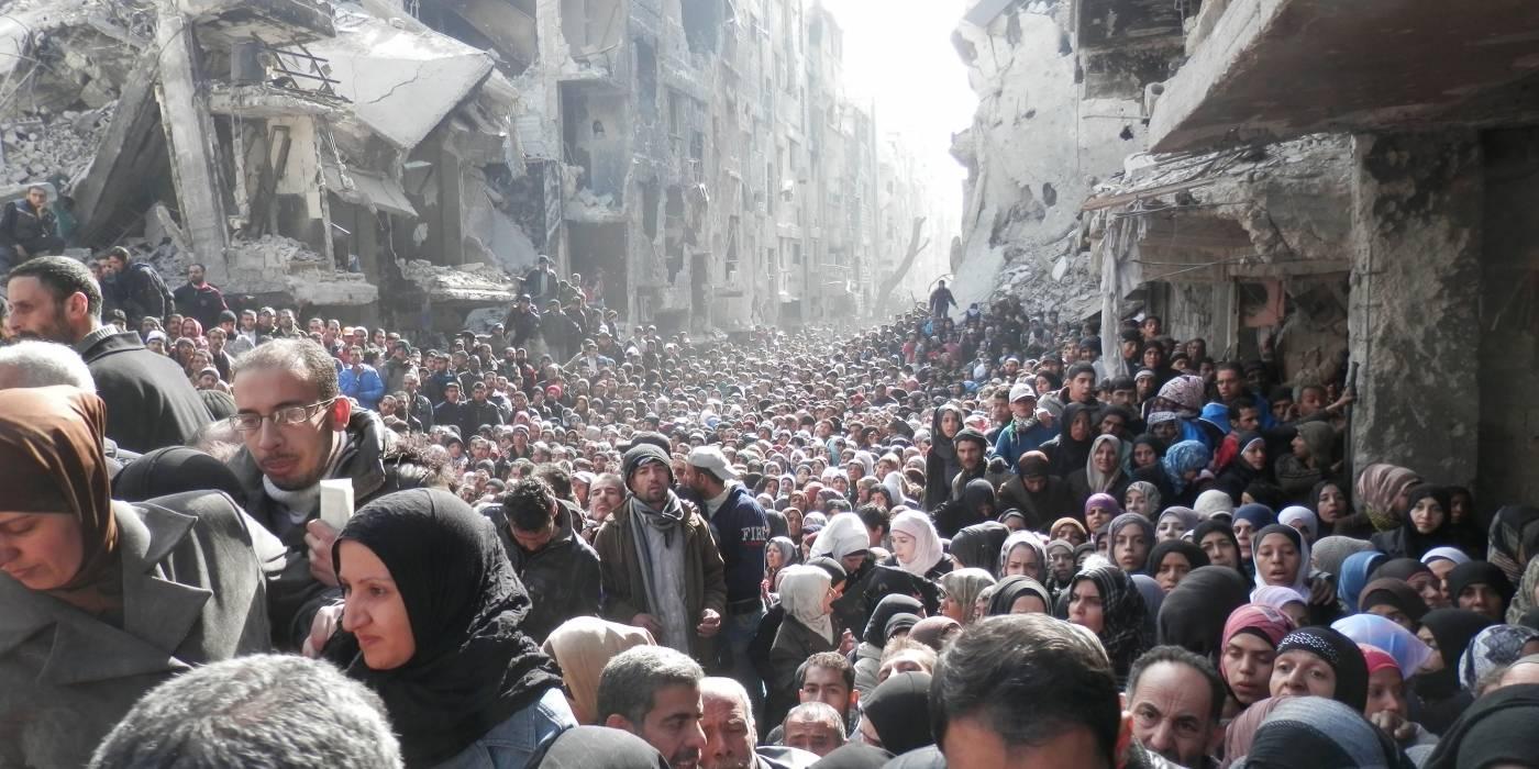 I den palæstinensiske flygtningelejr Yarmouk i Damaskus har adgangen til mad været meget begrænset under krigen. Befolkningen står i kø for at få madforsyninger fra FN, januar 2014 (Foto: Zuma Press / UNRWA).