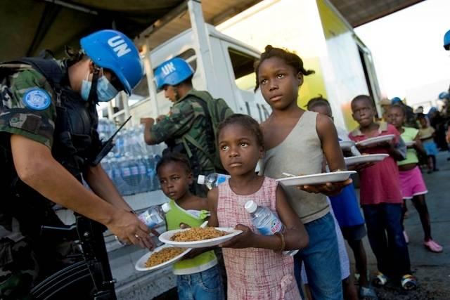 FNs fredsstyrker deler ut vann og mat til innbyggerne fra Cite Solei, på bildet er det barnas tur i køen. Bilde: UN Photo/Marco Dormino