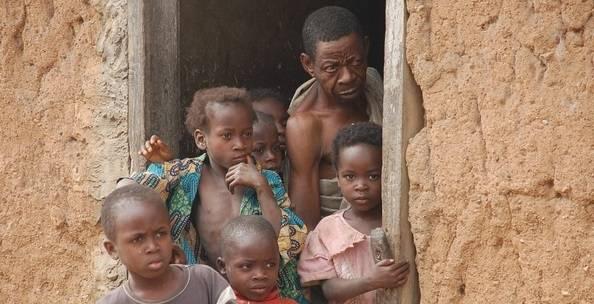 Børn og far kigger ud af lerhus i Nigeria (Foto: International Institute of Tropical Landbrug / Flickr).