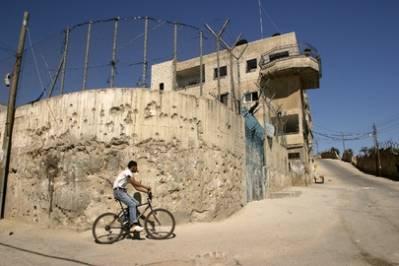 Dreng i flygtningelejren Aida i Bethlehem, der cykler langs israelernes mur, der forhindrer palæstinenserne på Vestbredden i frit at bevæge sig mellem Israel og Palæstina. 2003, UN Photo/Stephenie Hollyman.