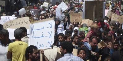 """Folk samles i byen Nawa, nær Deraa i en af de første demonstrationer mod regimet i april 2011. På skiltet står der """"Ingen vand, ingen medicin, ingen mad."""""""