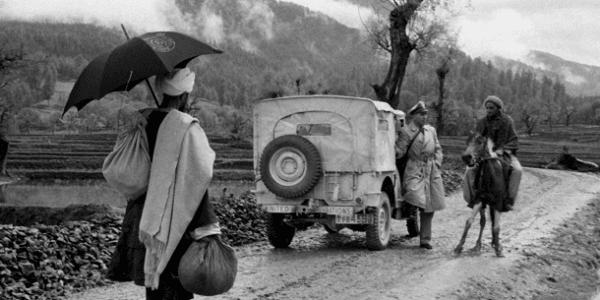 En FN- observatør har stoppet bilen og spørger en lokal mandpå hest om vej1955. Foto: UN Photo / SC
