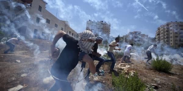 Palæstinensere demonstrerer mod krigen i Gaza i august 2014 og bliver mødt med tåregas. Foto: AP/Majdi Mohammed
