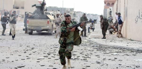 En soldat løber i dækning under kampen om byen Sirte i slutningen af Gaddafis tid ved magten, 19. oktober 2011. Foto: NTB Scanpix/AFP photo/Ahmad al-Rubaye