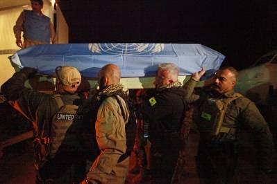 Kisten til en af de syv omkomne FN-ansatte, efter angrebet på UNAMA-basen i 2011, bliver båret til flyet som skal fragte den hjem. Foto: UN Photo/Eric Kanalstein