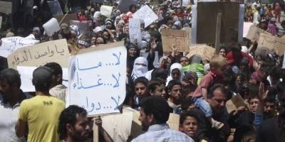 """Folk samles i byen Nawa, nær Deraa i en af de første demonstrationer mod regimet i april 2011. På skiltet står der """"Ingen vand, ingen medicin, ingen mad."""" (Foto: REUTERS / Handout)."""